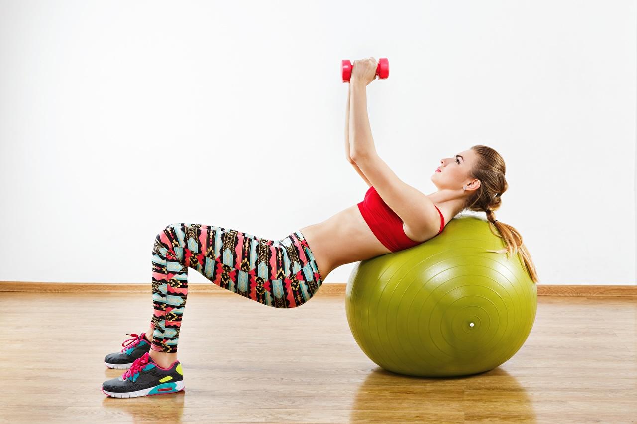 Bilder Körperliche Aktivität Pose Fitness Hanteln Mädchens sportliches Ball Hand Trainieren posiert Sport Hantel junge frau junge Frauen