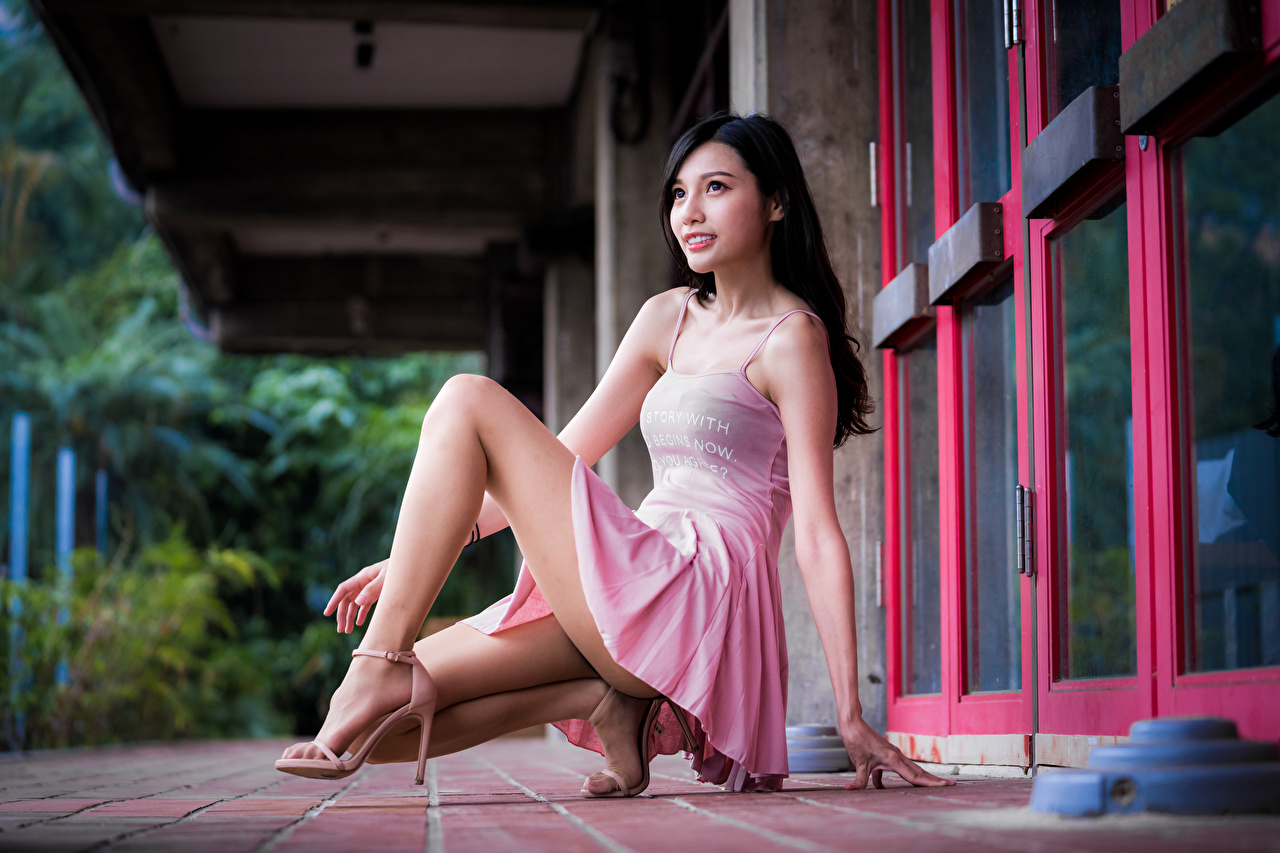 Desktop Wallpapers Brunette girl Girls Legs Asiatic Sitting Staring Dress female young woman Asian sit Glance gown frock