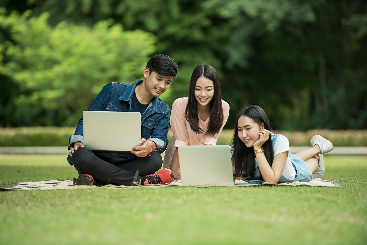Picture Laptops Brunette girl Female students Man female sit Grass Three 3 Men Girls young woman Sitting