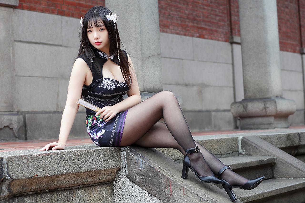 Desktop Hintergrundbilder Brünette Fächer dekolletee junge Frauen Bein Asiatische sitzen Starren Kleid High Heels Dekolleté Mädchens junge frau Asiaten asiatisches sitzt Sitzend Blick Stöckelschuh