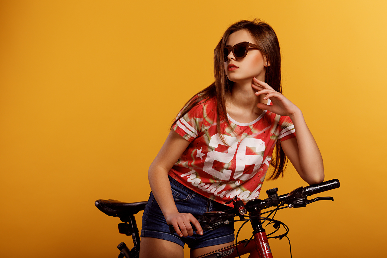 Images Viacheslav Krivonos Brown haired Lera Bicycle T-shirt young woman Hands Shorts Glasses Colored background bike bicycles Girls female eyeglasses