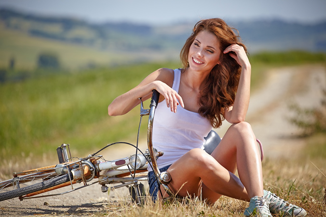 Picture Girls Sitting Redhead girl Legs Grass blurred background Hands Singlet Smile Bicycle Izabela Magier female young woman sit Bokeh Sleeveless shirt bike bicycles