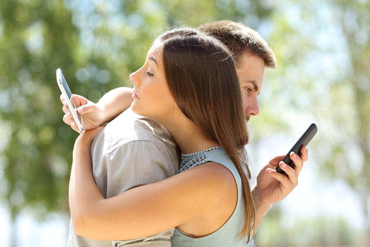Bilder von Smartphone jugendlich Bokeh Zwei umarmen Mädchens kerl smartphones Junger Mann unscharfer Hintergrund 2 umarmt Umarmung junge frau junge Frauen