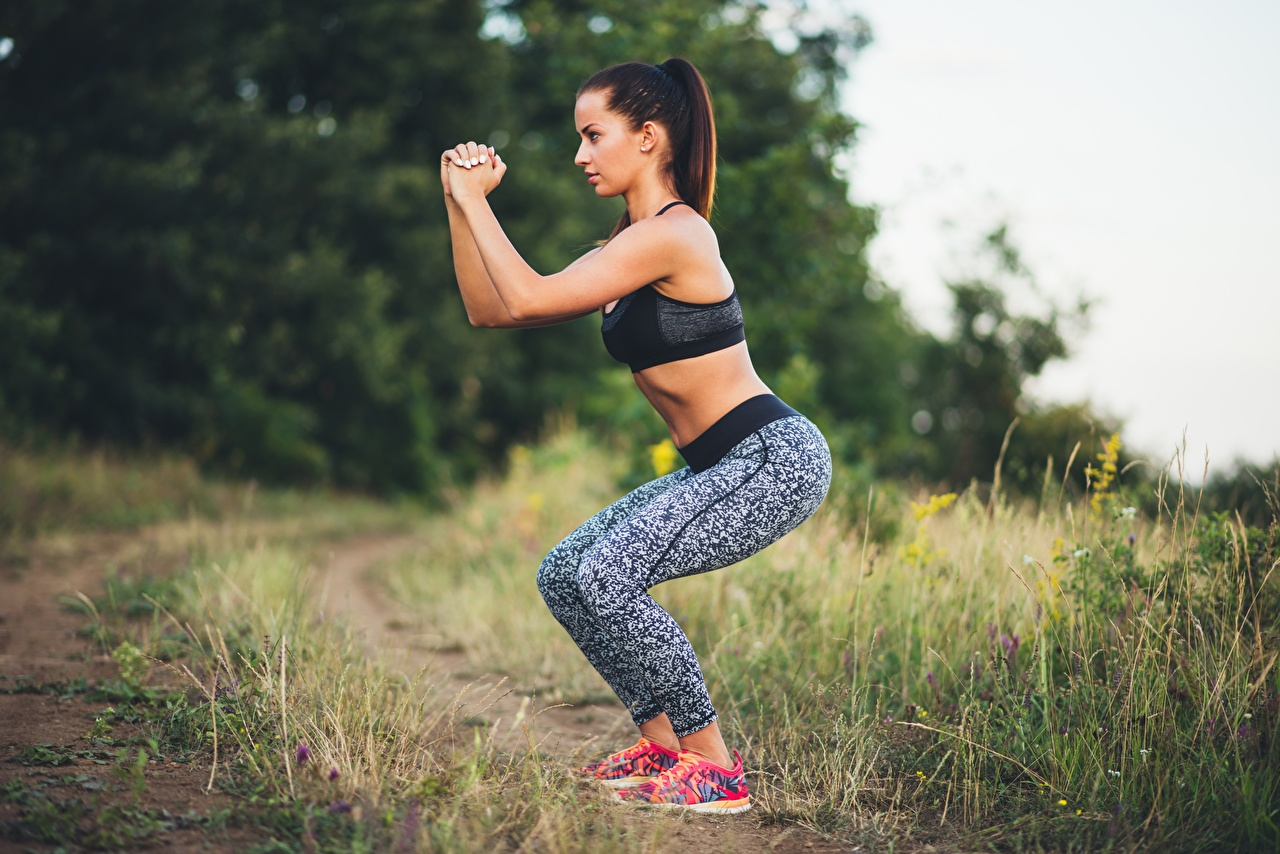 Picture Brown haired Bokeh posing Fitness Girls Sport Side Grass Hands blurred background Pose female sports athletic young woman