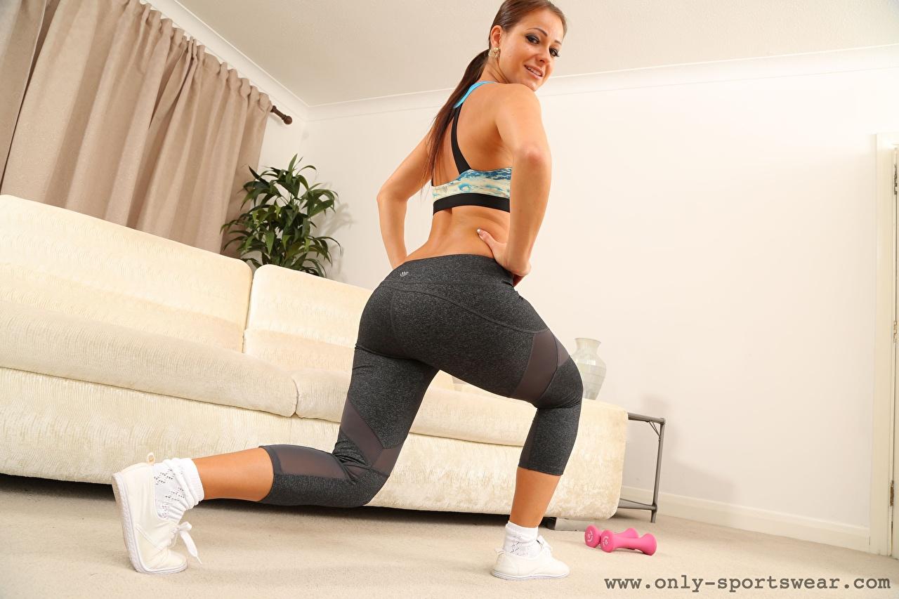 Foto Melisa Mendiny Trainieren Lächeln Fitness junge frau Bein Hand Blick Körperliche Aktivität Mädchens junge Frauen Starren