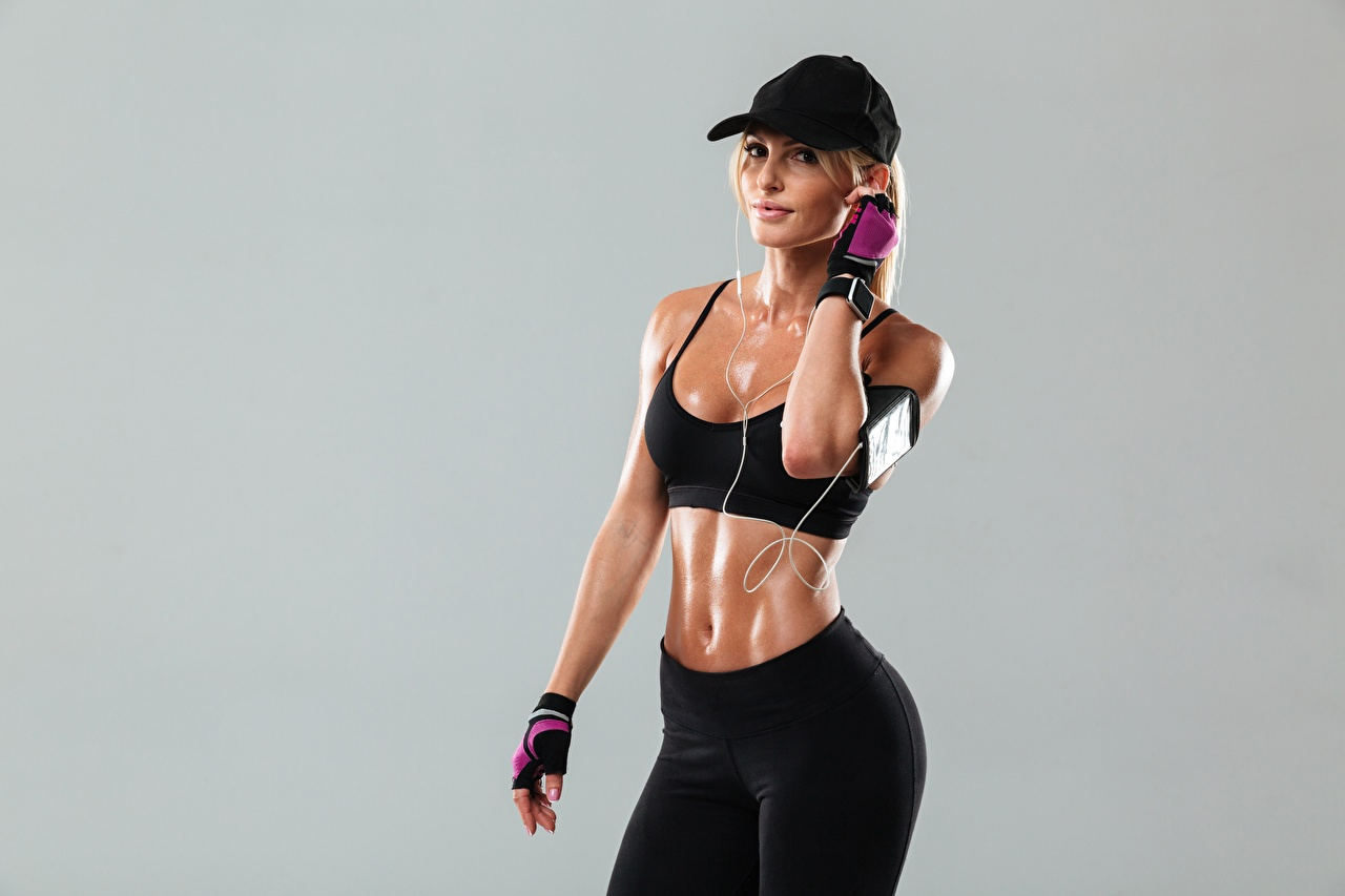 Images Headphones Blonde girl Glove Fitness Girls Sport Belly Staring Baseball cap Gray background female sports athletic young woman Glance