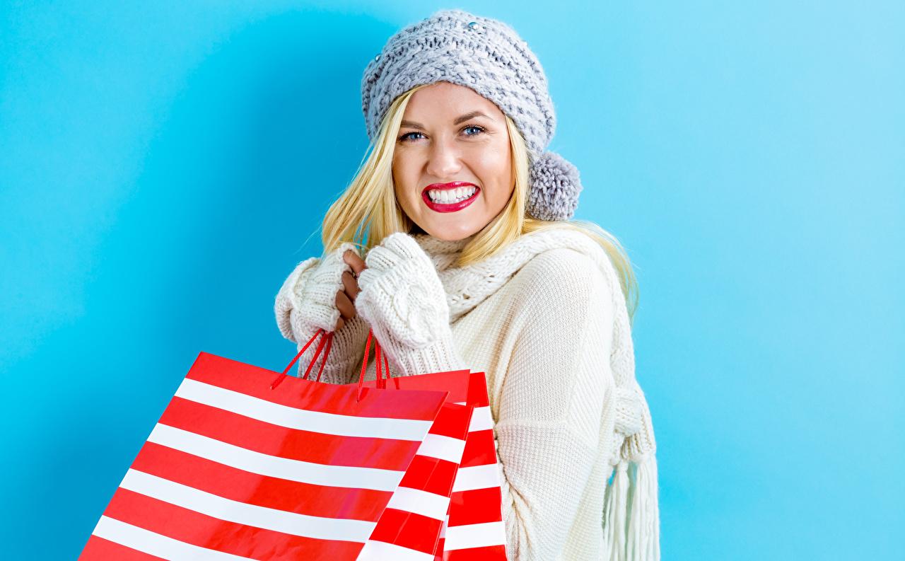 Foton Blond tjej Leende Handskar Papperspåse Vinterhatt Unga kvinnor Blick Röda läppar Färgad bakgrund ung kvinna ser