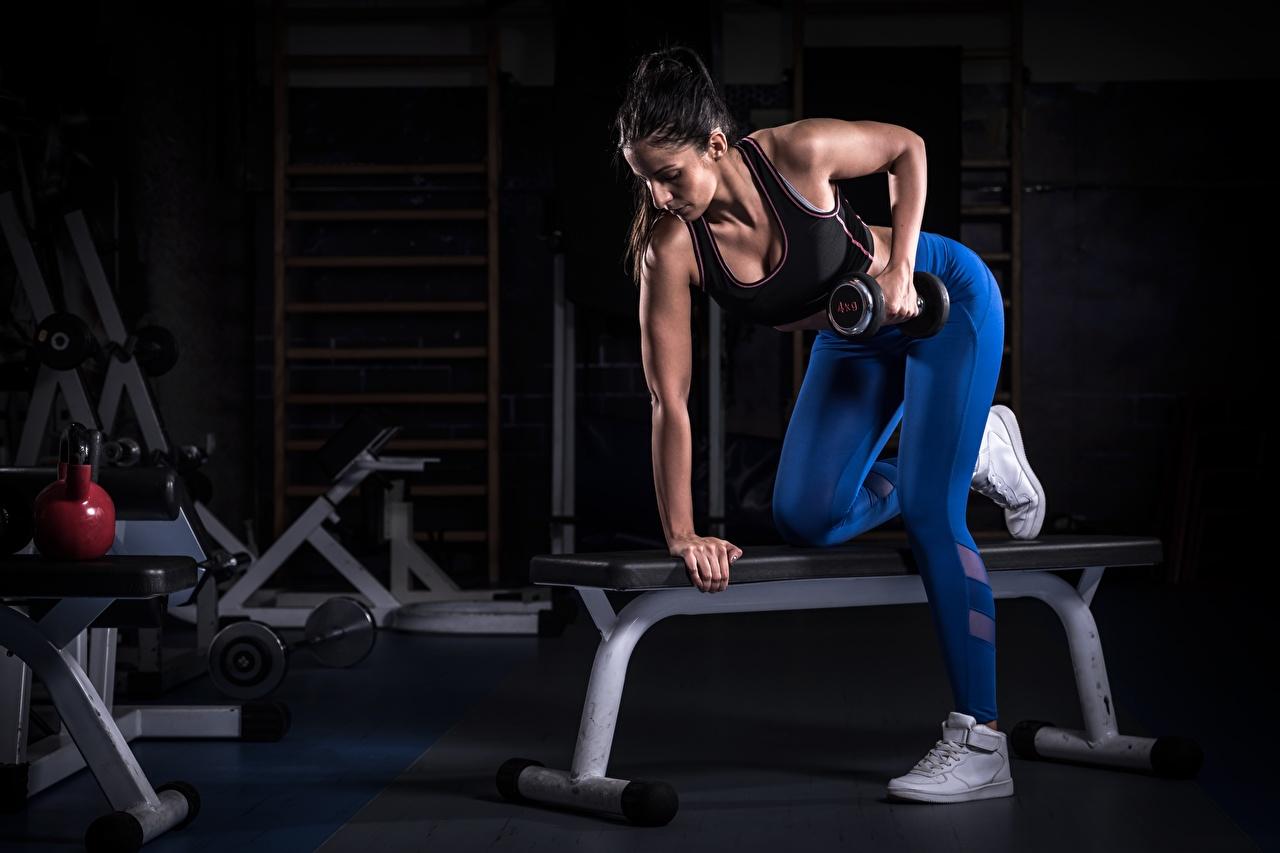 Bilder Brünette Trainieren Fitnessstudio Fitness Hantel Mädchens sportliches Hand Turnhalle Körperliche Aktivität Sport Hanteln junge frau junge Frauen