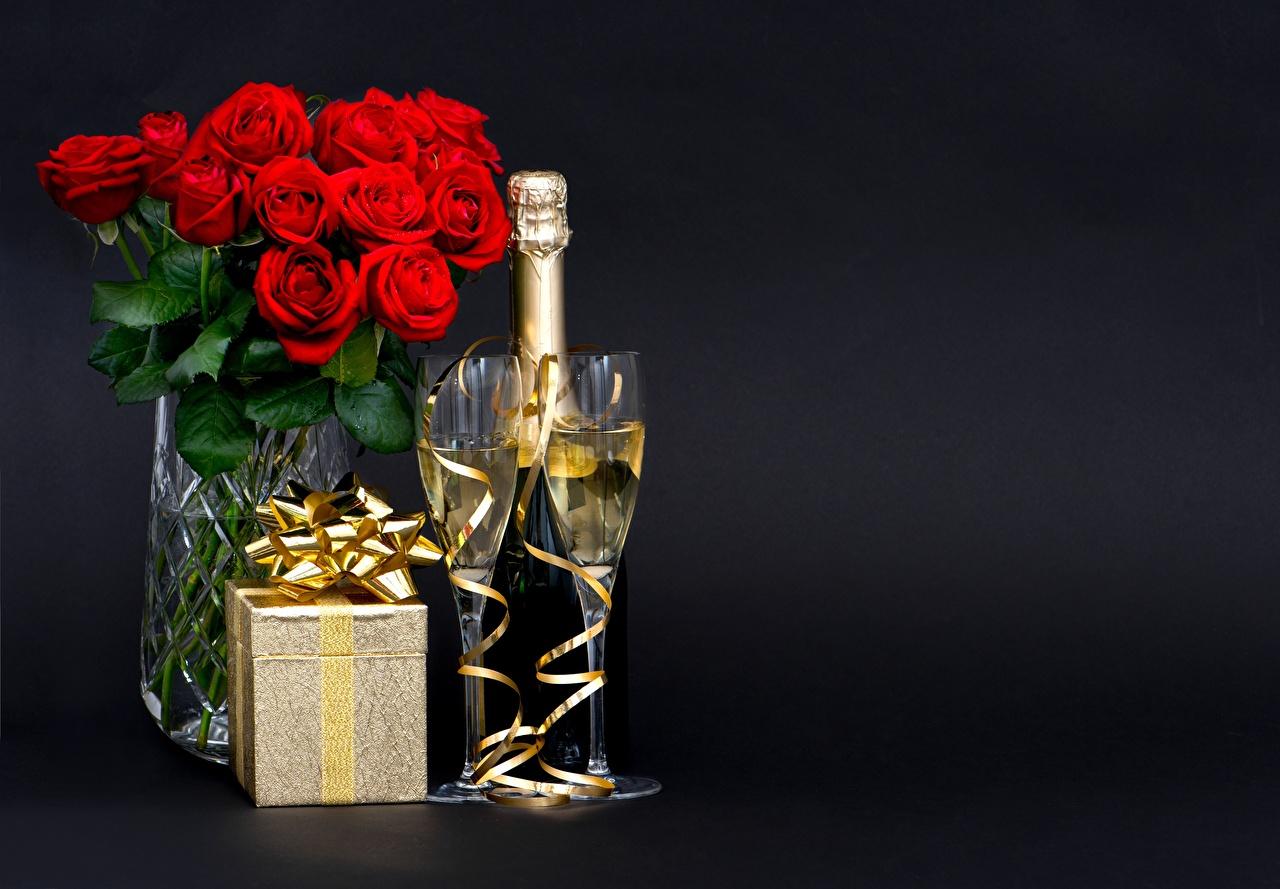 Fotos Blumensträuße Rosen Champagner Blüte Schachtel Geschenke Weinglas Schleife das Essen Schwarzer Hintergrund Sträuße Rose Schaumwein Blumen Lebensmittel