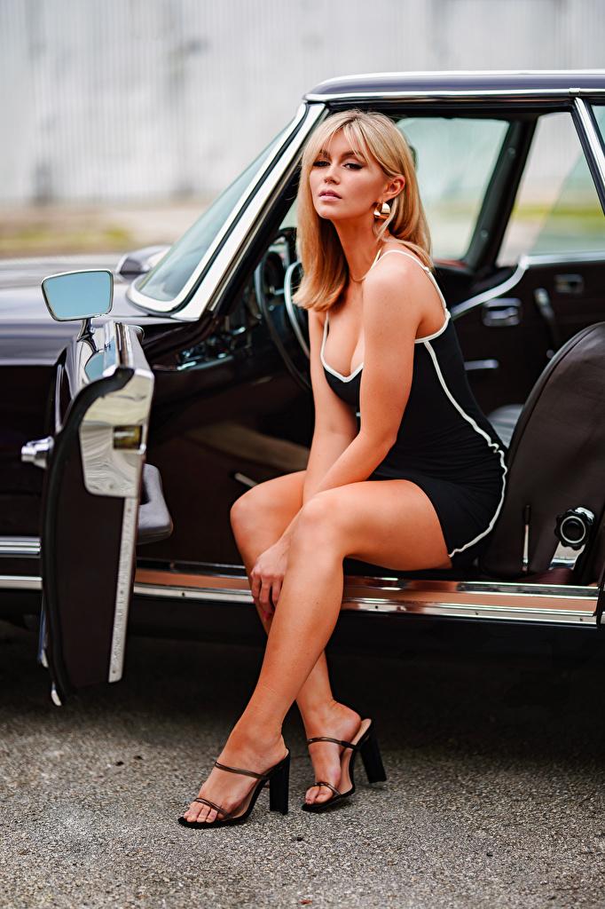 Fotos Blondine Marina junge Frauen Bein sitzt Autos Starren Kleid  für Handy Blond Mädchen Mädchens junge frau auto sitzen Sitzend automobil Blick