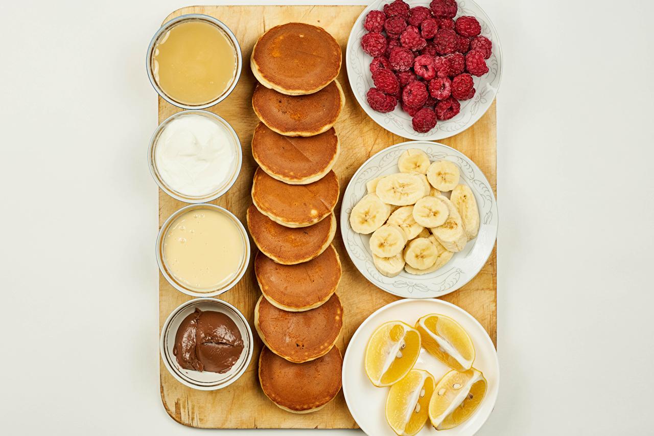 Bilder på skrivbordet Choklad Honung Grädde Pannkakor Apelsin frukt Hallon Bananer Mat Skärbräda Grå bakgrund pannkaka skärbräde