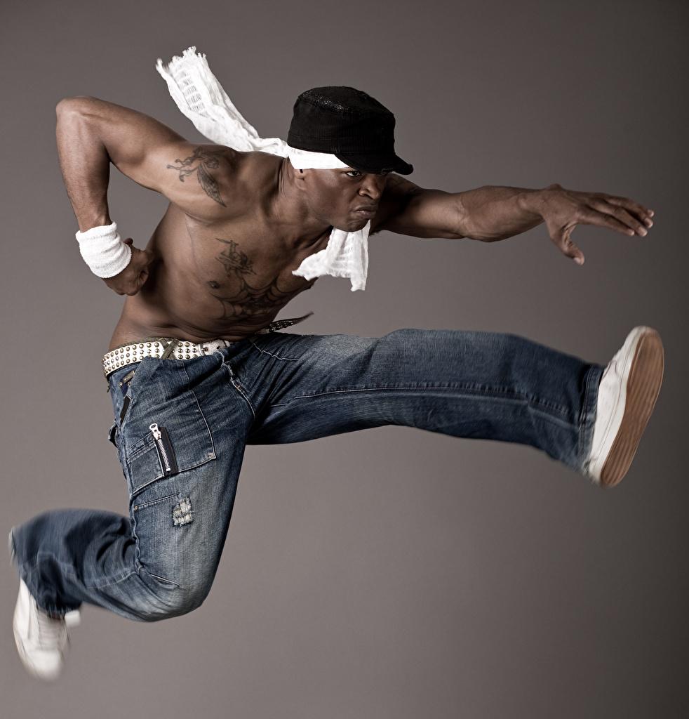 Bilder Mann Tanz Neger Jeans Sprung Hand Baseballcap Grauer Hintergrund Tanzen