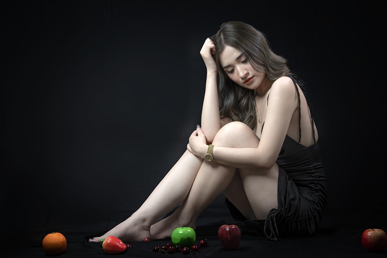 Desktop Hintergrundbilder Brünette junge Frauen Bein Äpfel asiatisches Hand sitzt Schwarzer Hintergrund Mädchens junge frau Asiaten Asiatische sitzen Sitzend