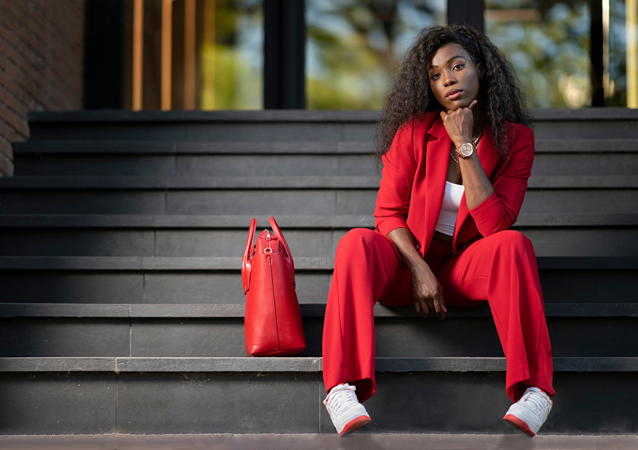 Image Ginette curls Red Girls Stairs Negroid Suit Handbag Sitting Glance Curly female stairway staircase young woman sit purse Staring