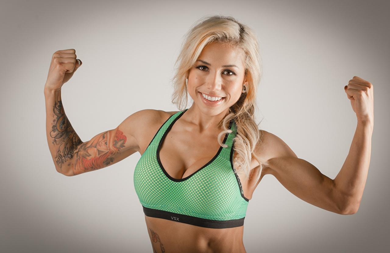 Foto Tatoeage Blonde Glimlach Pose Fitness jonge vrouw hand Kijkt Grijze achtergrond Blond meisje poseren Jonge vrouwen Handen