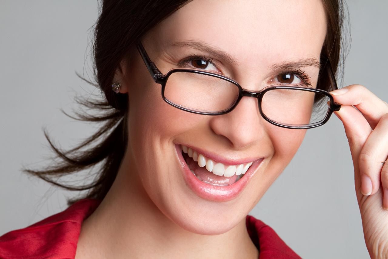 Images Brunette girl Smile Face Girls Teeth Fingers Glasses Gray background female young woman eyeglasses