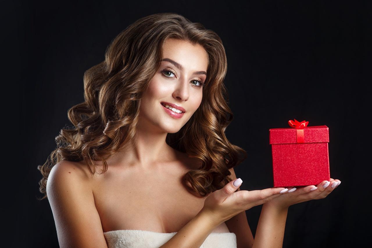 Fotos von Braunhaarige Frisur Haar Mädchens Geschenke Schachtel Hand Blick Schwarzer Hintergrund Braune Haare Frisuren junge frau junge Frauen Starren