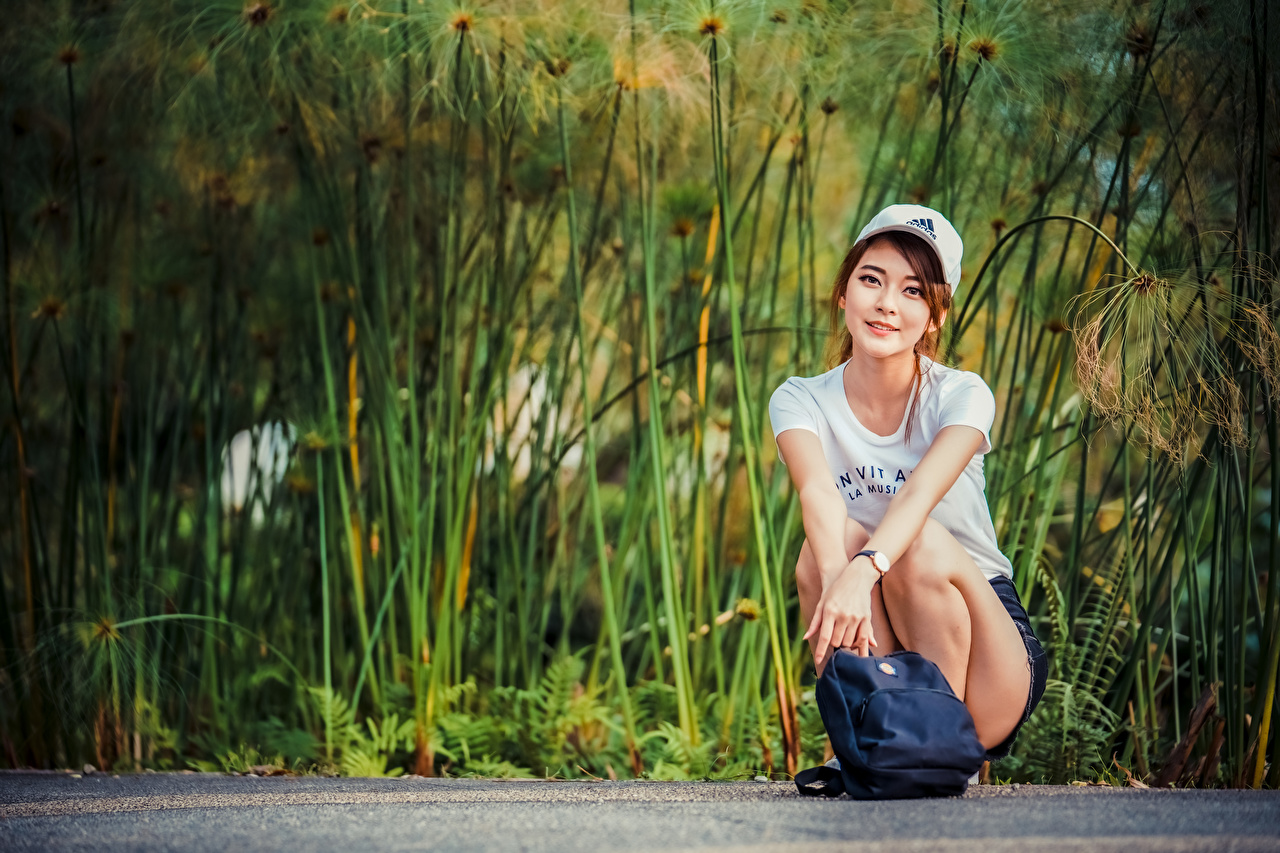 Photo T-shirt young woman Asian purse Sitting Glance Baseball cap Girls female Asiatic sit Handbag Staring
