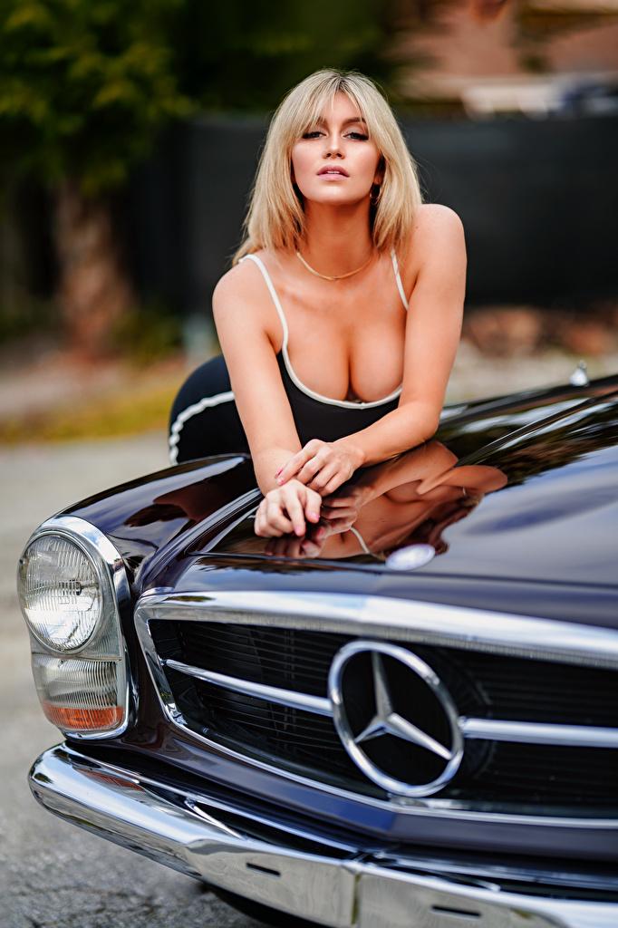 Bilder Blond Mädchen Bokeh Dekolleté junge frau Autos Starren Kleid  für Handy Blondine unscharfer Hintergrund dekolletee Mädchens junge Frauen auto automobil Blick