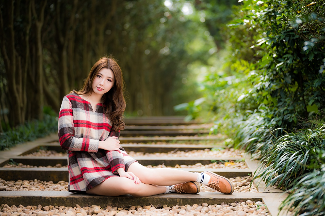Desktop Wallpapers Brown haired blurred background young woman Legs Asian sit Hands Bokeh Girls female Asiatic Sitting