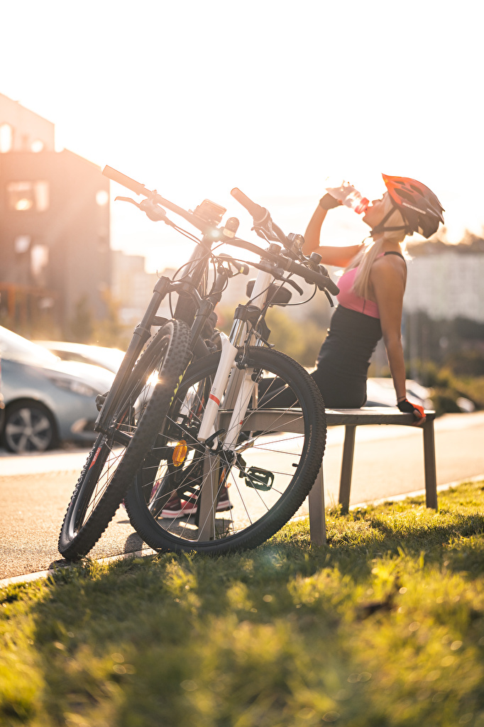 Photo Helmet Drinking bike Rest female Sunrises and sunsets Grass Bench Sitting  for Mobile phone Bicycle bicycles relax Girls Resting young woman sunrise and sunset sit