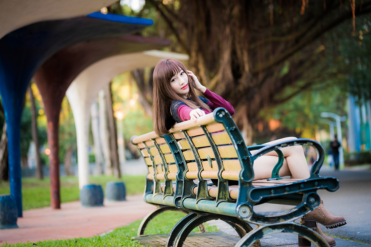 Photos Brown haired blurred background female Asiatic sit Bench Staring Bokeh Girls young woman Asian Sitting Glance