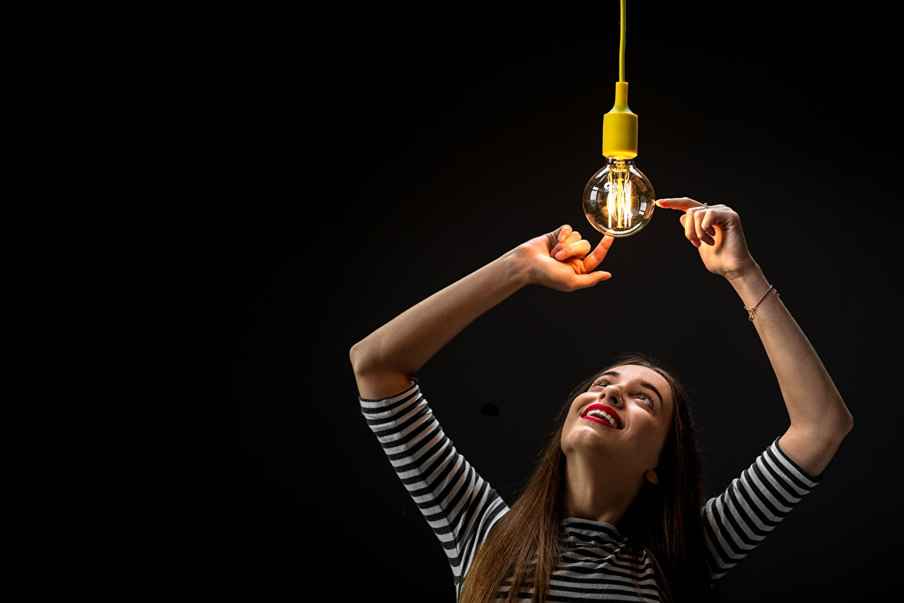Photo Brown haired Smile Girls Light bulb Hands Black background female young woman