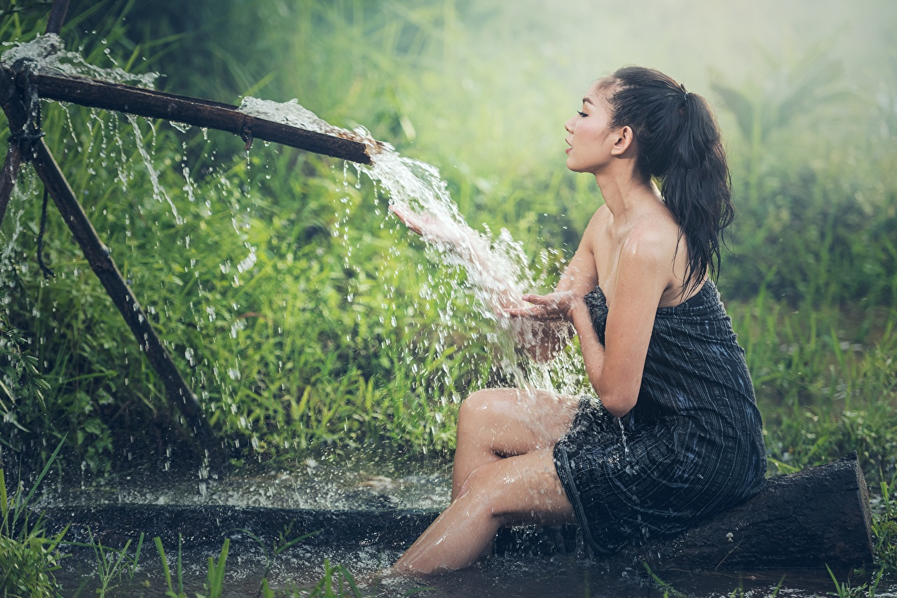 Photos Brunette girl Girls Asiatic Water splash sit Wet female young woman Asian Sitting