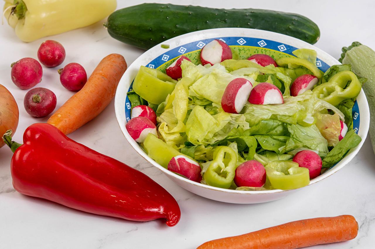 Fotos von Gurke Mohrrübe Radieschen Teller Paprika Gemüse Lebensmittel das Essen