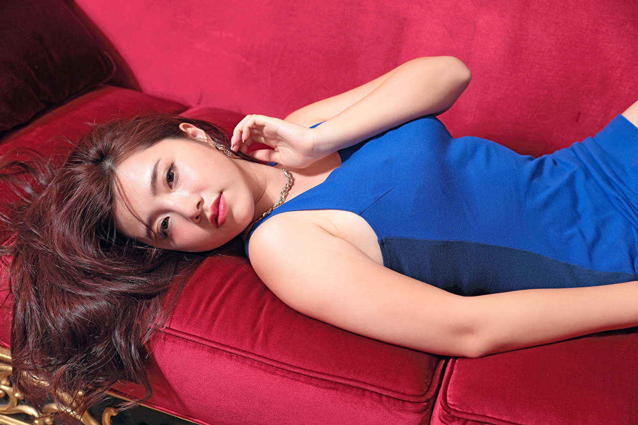 Pictures Brown haired esting young woman Asian Hands Glance Dress laying Lying down Girls female Asiatic Staring gown frock