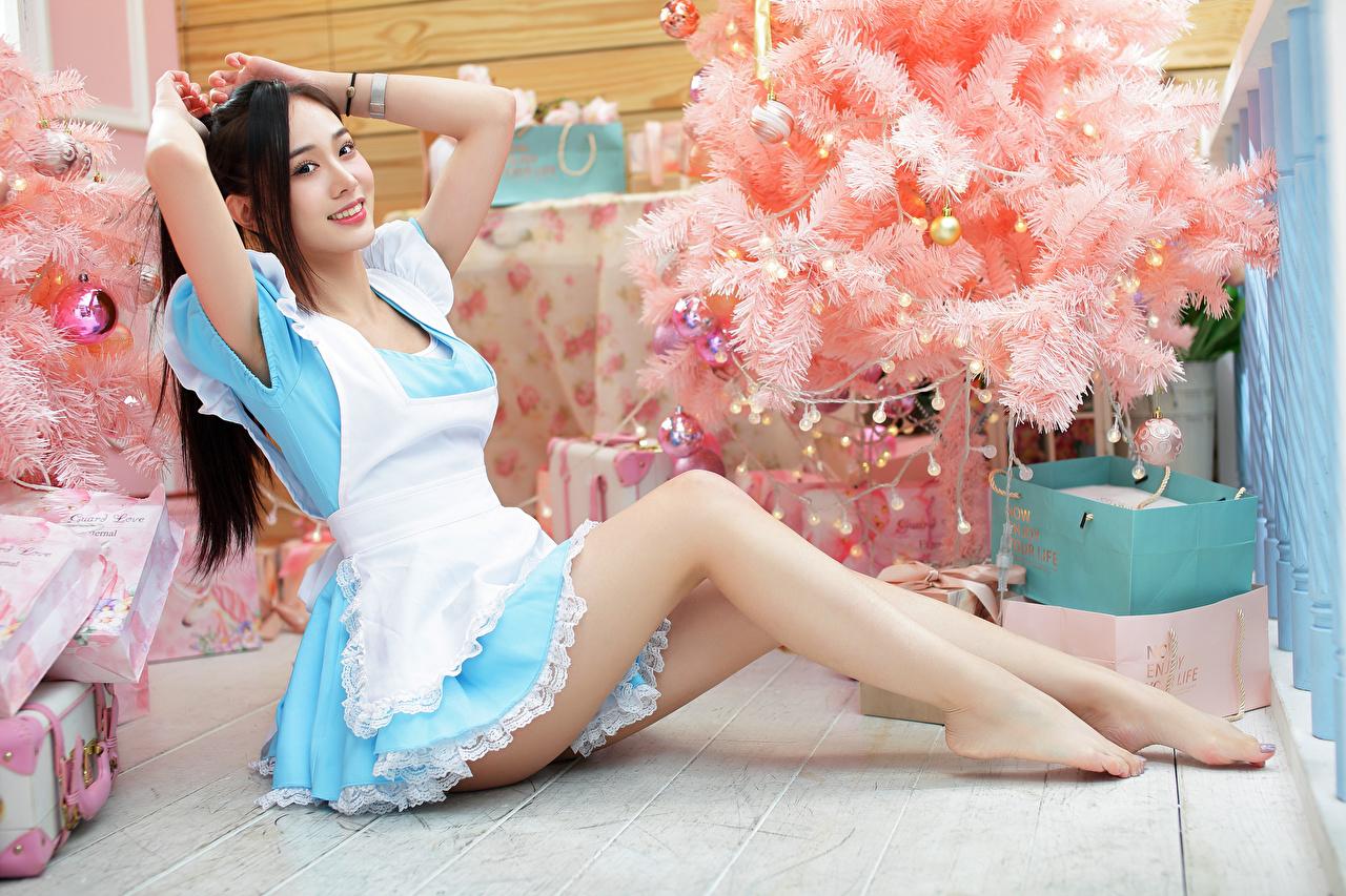 Foto Brünette Lächeln Mädchens Tannenbaum Bein Asiatische sitzt Uniform Blick junge frau Christbaum junge Frauen Weihnachtsbaum Asiaten asiatisches sitzen Sitzend Starren