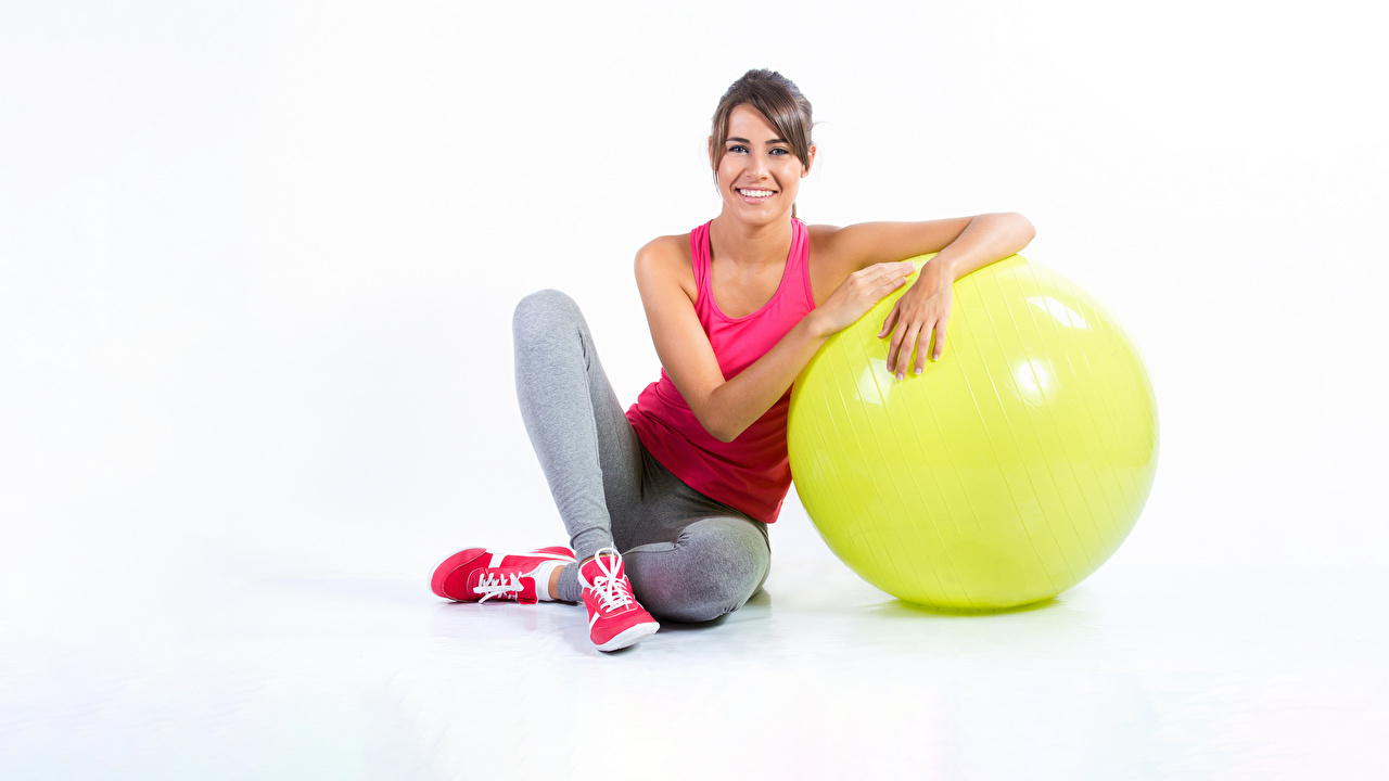 Photos Smile Fitness Sport Girls Ball Sitting Staring White background sports female athletic young woman sit Glance