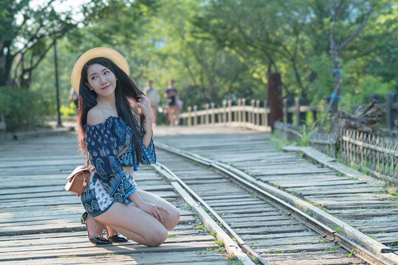 Photo Brunette girl blurred background Pose Hat Girls Legs Asiatic purse Hands Bokeh posing female young woman Asian Handbag
