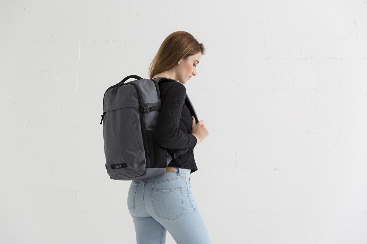 Desktop Hintergrundbilder Braunhaarige Rucksack junge Frauen Jeans Sweatshirt Grauer Hintergrund Braune Haare Mädchens junge frau