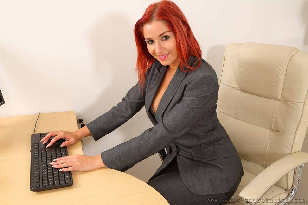 Pictures Harley Geck Keyboard Redhead girl Secretaries Smile young woman sit Suit Hands Wing chair Glance Girls female Sitting Armchair Staring