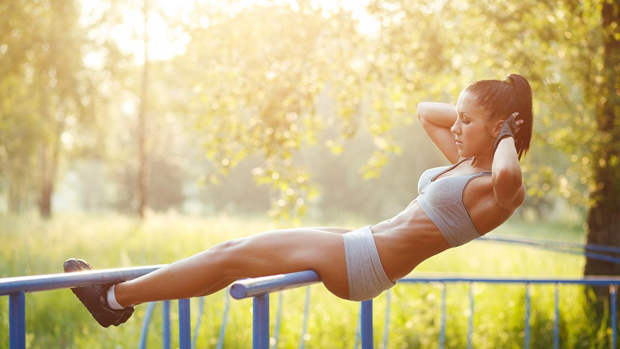 Fotos Brünette Trainieren unscharfer Hintergrund Fitness Sport Mädchens Bein Hand Seitlich Körperliche Aktivität Bokeh junge frau sportliches junge Frauen