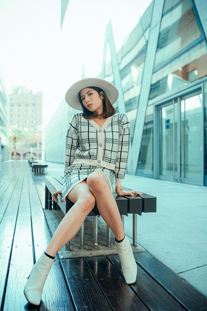 Fotos Der Hut junge Frauen Bein Asiaten sitzt Blick  für Handy Mädchens junge frau Asiatische asiatisches sitzen Sitzend Starren