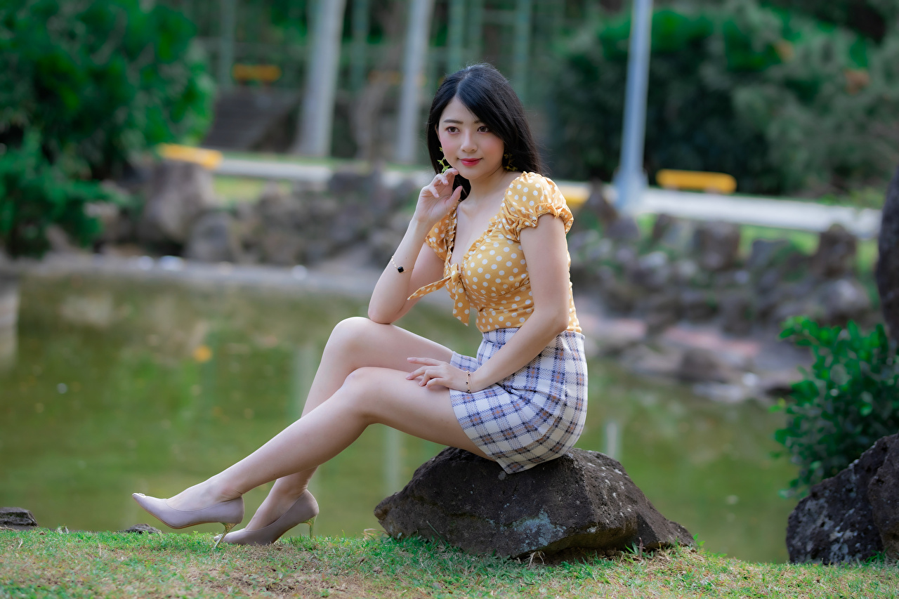 Desktop Wallpapers Skirt Blouse Girls Legs Asian sit Stones Glance high heels female young woman Asiatic stone Sitting Staring Stilettos