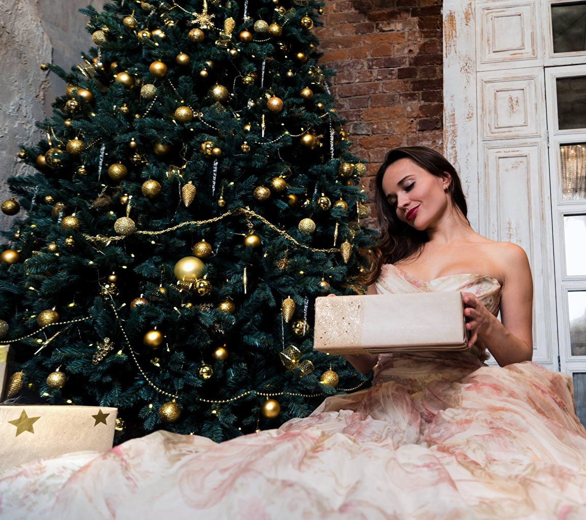 Photo Christmas Brown haired young woman New Year tree Gifts sit gown New year Girls female Christmas tree present Sitting Dress frock