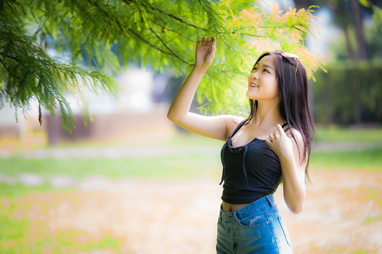 Pictures Brunette girl Smile Bokeh Girls Asiatic Hands Branches blurred background female young woman Asian