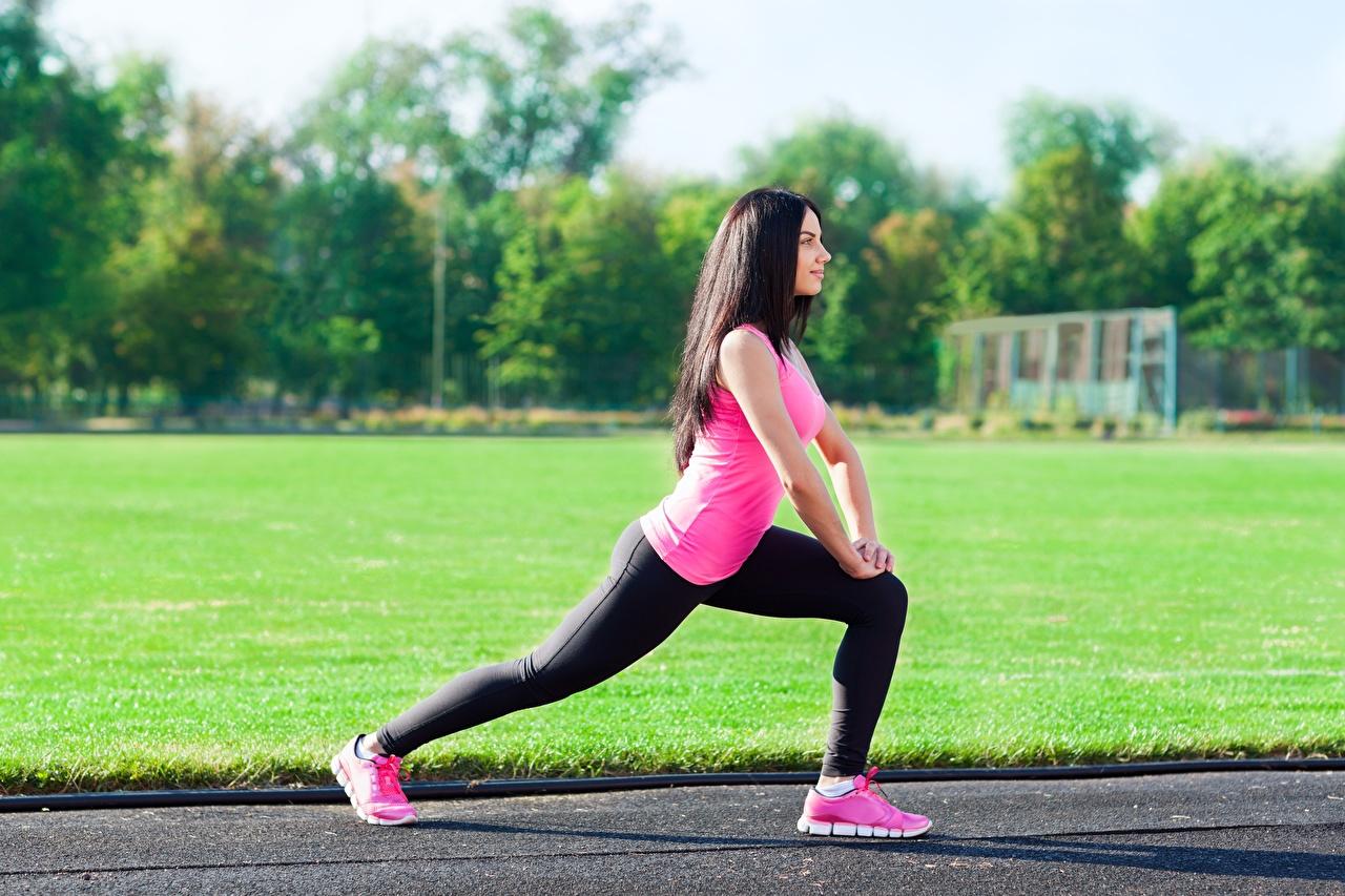 Fotos von Brünette Dehnübungen unscharfer Hintergrund Fitness Turnschuh Mädchens Bein Hand Uniform Seitlich Dehnübung Bokeh junge frau sportschuhe junge Frauen