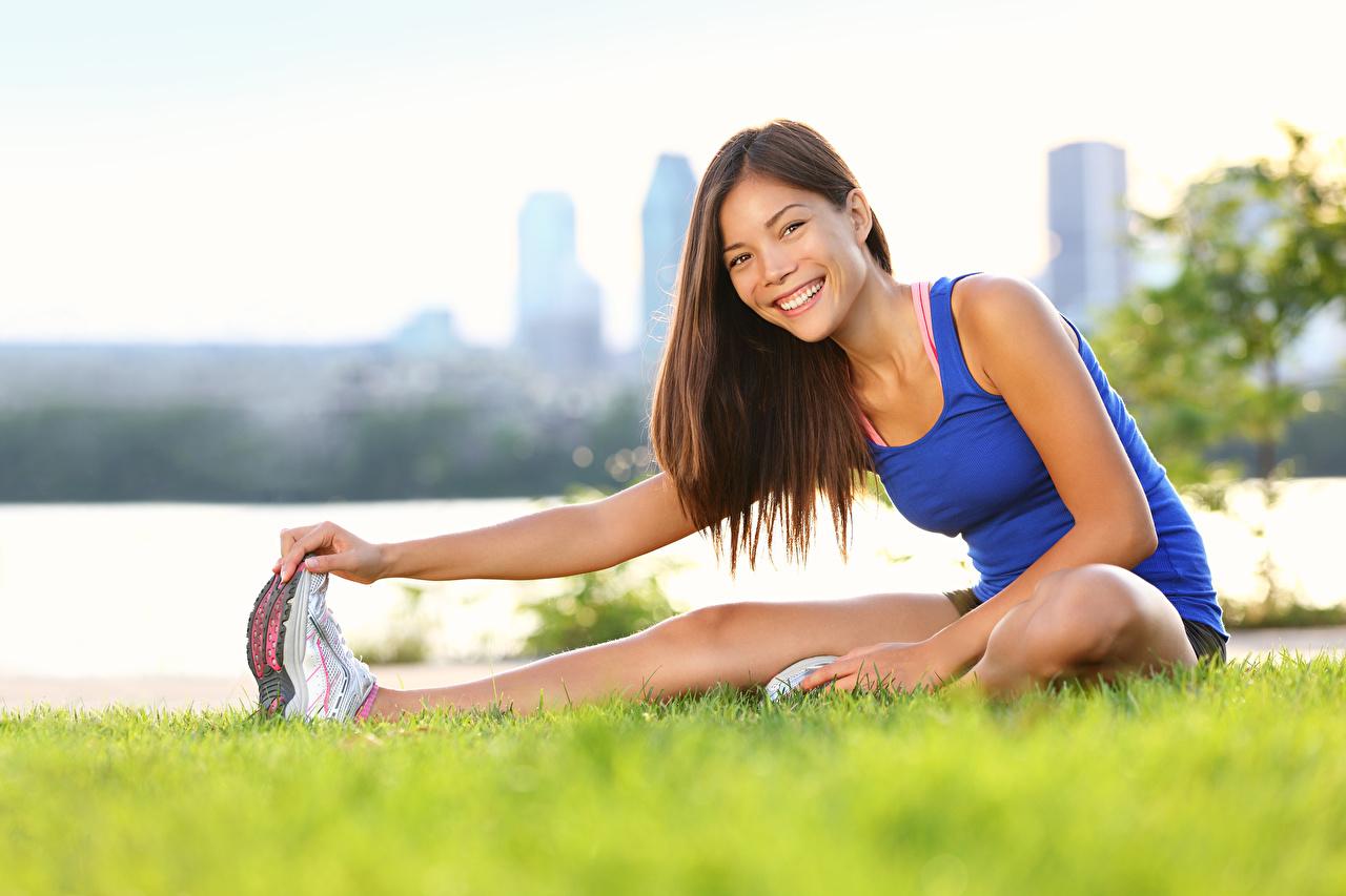 Fotos von Braunhaarige Lächeln Dehnübungen Fitness Mädchens Asiatische Gras sitzen Braune Haare Dehnübung junge frau junge Frauen Asiaten asiatisches sitzt Sitzend