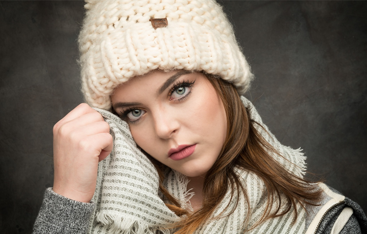 Picture Brown haired female Winter hat Hands Staring Gray background Girls young woman Glance
