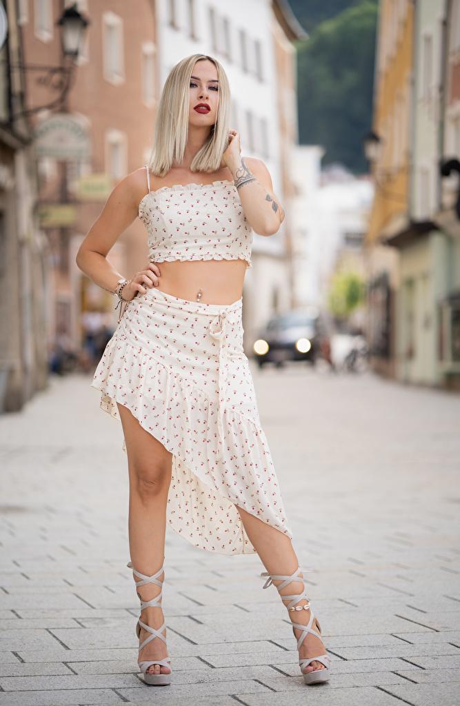 Fotos Rock Blondine unscharfer Hintergrund Pose Mädchens Bein Hand High Heels  für Handy Blond Mädchen Bokeh posiert junge frau junge Frauen Stöckelschuh