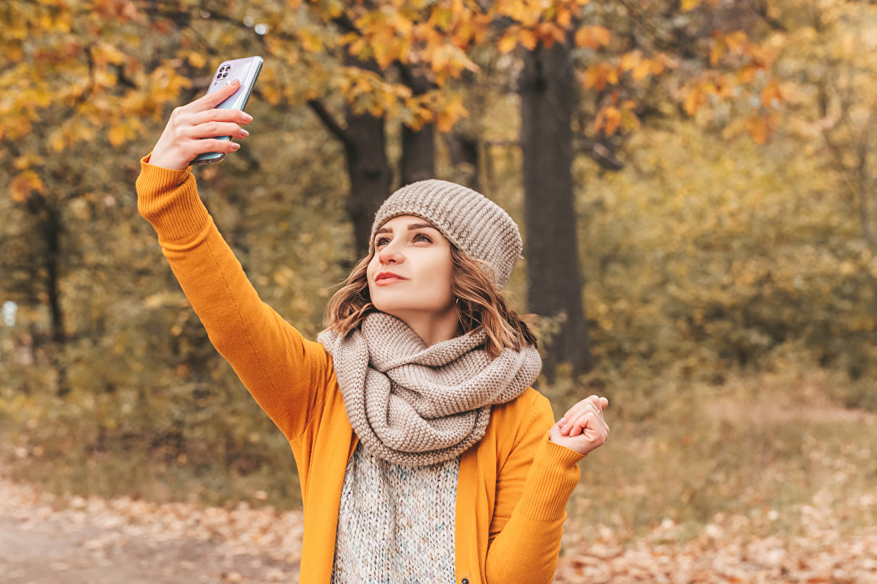 Desktop Wallpapers Brown haired Scarf Selfie smartphones Bokeh Girls Autumn Winter hat Hands Smartphone blurred background female young woman
