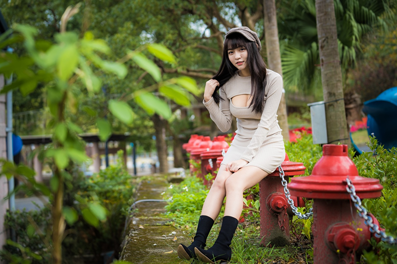 Pictures Brunette girl Wearing boots Décolletage Girls Legs Asian Chain sit Hands Baseball cap Dress neckline decollete female young woman Asiatic Sitting gown frock