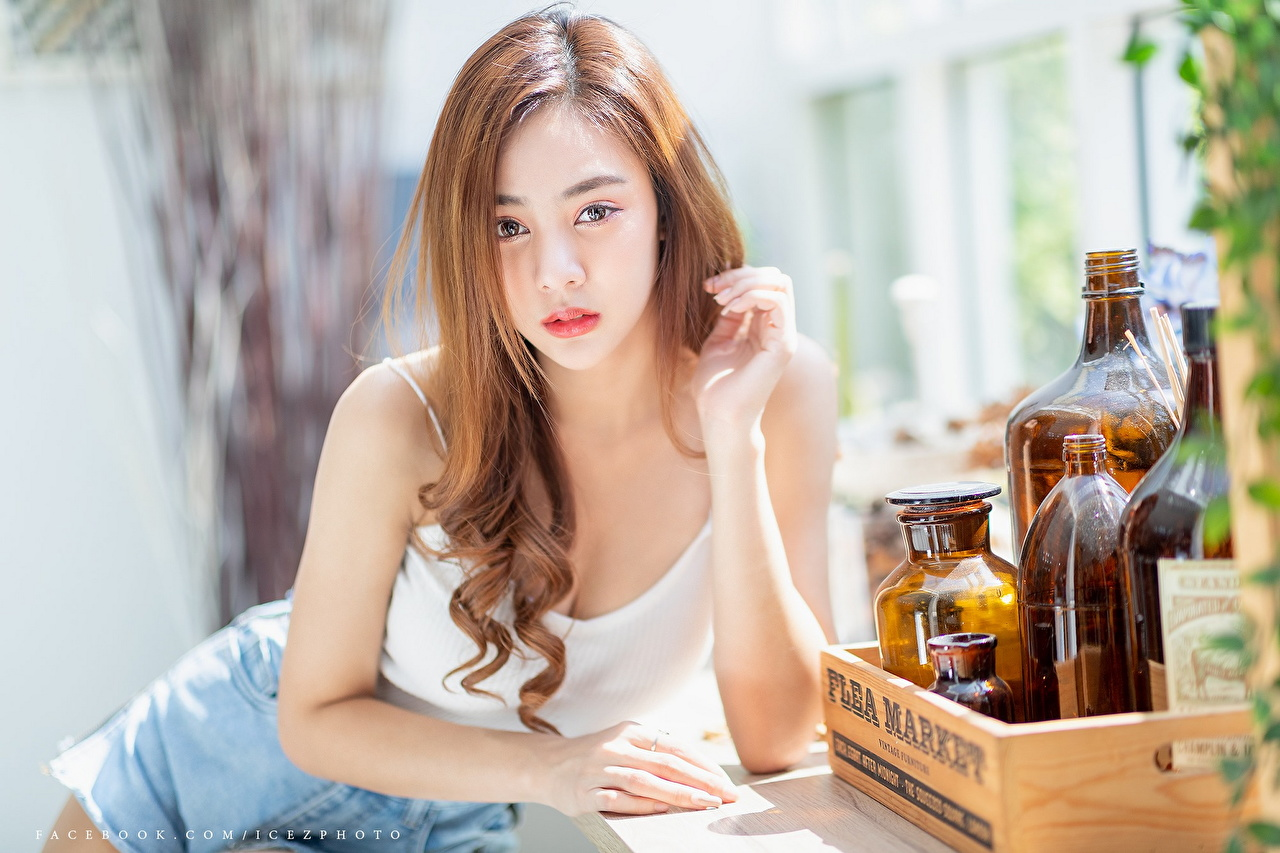 Image Brown haired blurred background Girls Asiatic Hands bottles Staring Bokeh female young woman Asian Bottle Glance