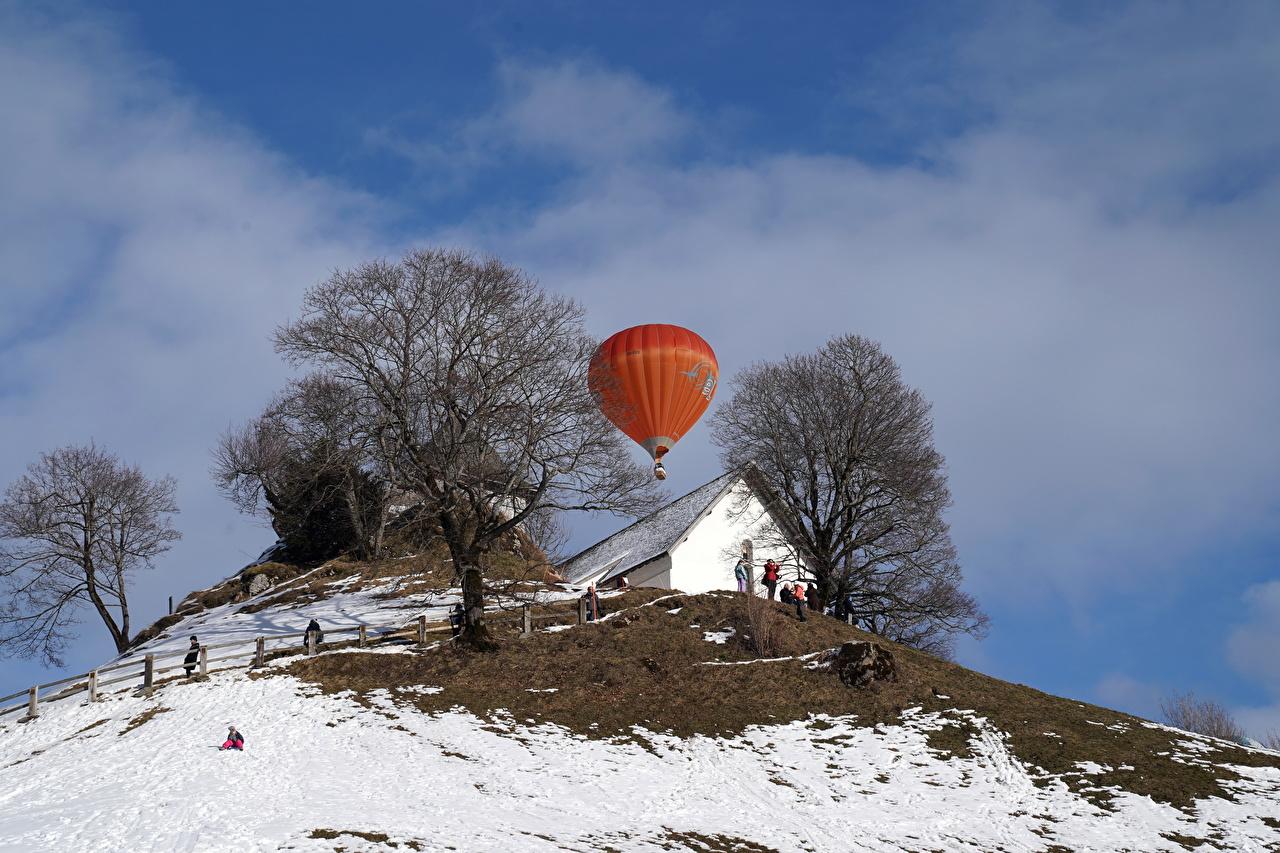 Bilder Fesselballon Natur Winter Schnee Hügel Bäume Gebäude heißluftballon Haus