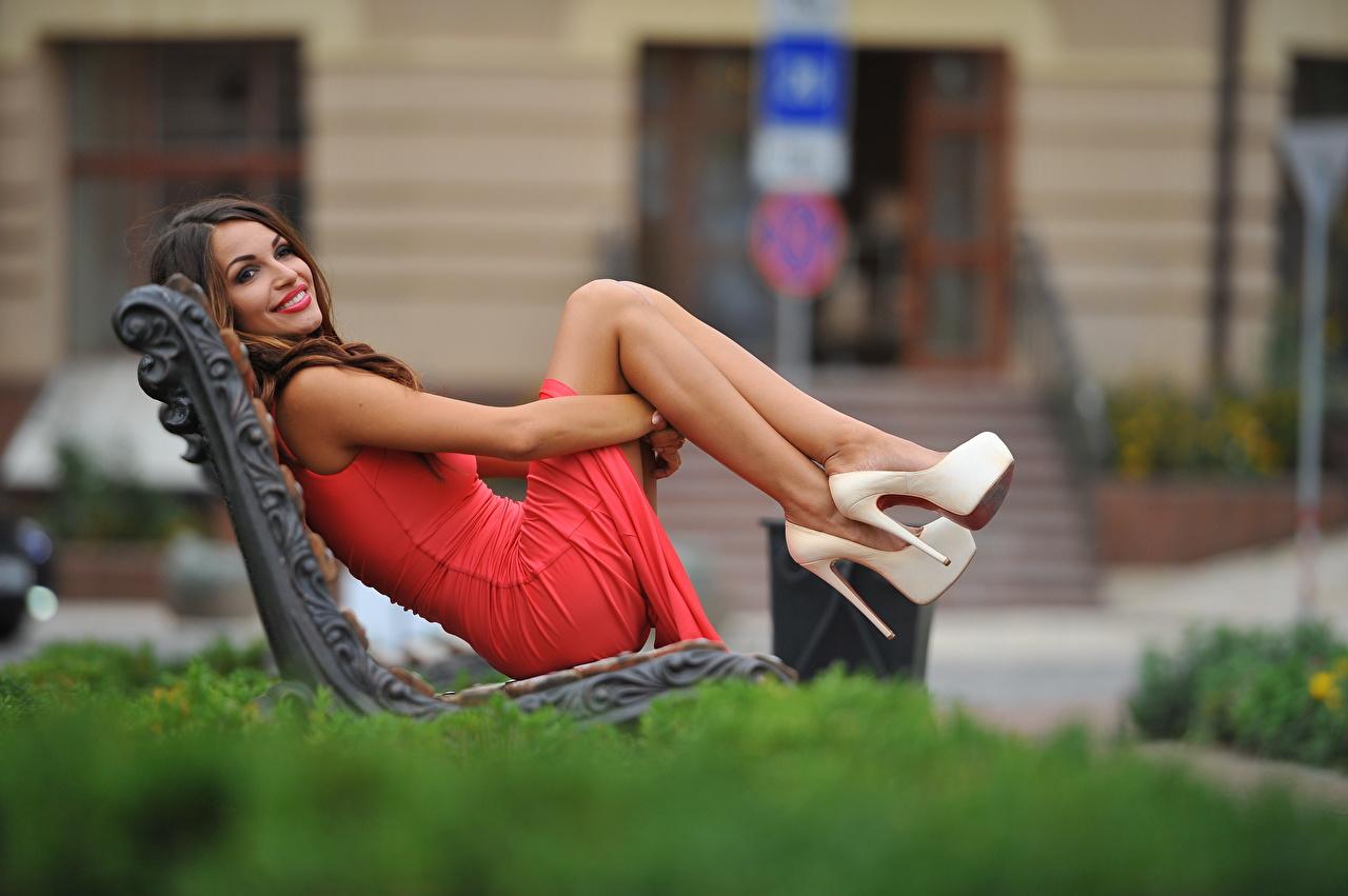 Fotos von Braunhaarige Lächeln unscharfer Hintergrund Mädchens Bein Hand Bank (Möbel) Kleid Stöckelschuh Braune Haare Bokeh junge frau junge Frauen High Heels