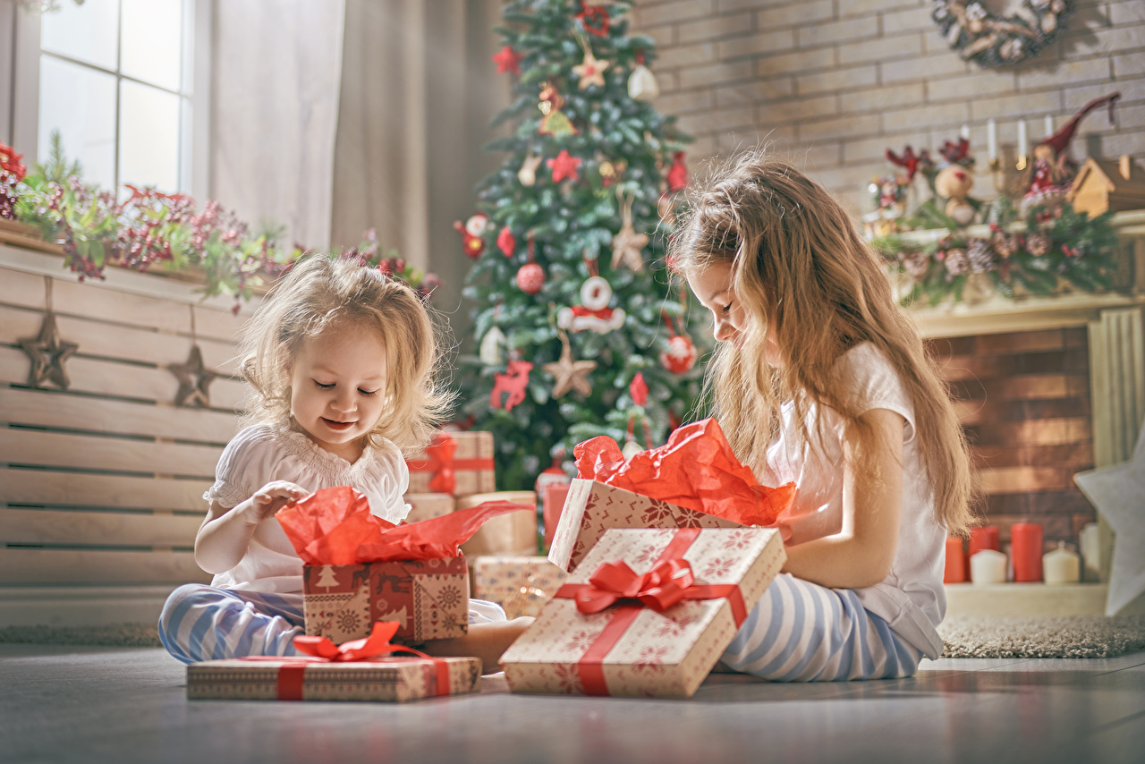 Photo Little girls New year Children Two present sit Holidays Christmas child 2 Gifts Sitting
